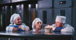 A gorgeous baker girl wearing a chefs attire makes a wish and blows out the candles on a cake , she is then applauded by. Two cheerful men stock video footage