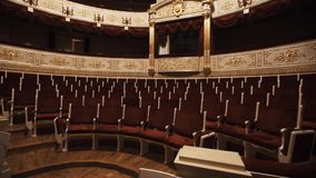 Gorgeous balcony in opera hall, empty chairs rows, red draipings. Golden decorations, beautiful mural stock video