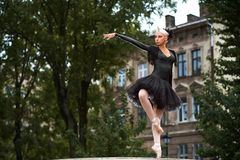 Gorgeous ballerina in black outfit dancing in the city streets. Stunning expressive ballet performance of a professional female dancer wearing black swan outfit Stock Image
