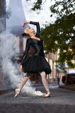 Gorgeous ballerina in black outfit dancing in the city streets royalty free stock photos