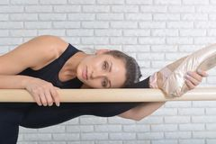 Gorgeous ballerina stretching in ballet class. She holds her left leg and hand on the ballet barre. Closeup portrait. Stock Photo