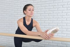 Gorgeous ballerina stretching in ballet class near the ballet barre.