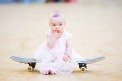 Gorgeous barefoot baby girl on skateboard Stock Photos