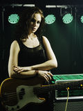 Gorgeous bass player. Photo of a beautiful young bass player standing on stage with her guitar Stock Images