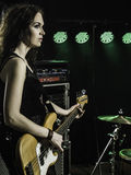 Gorgeous bass player on stage. Photo of a beautiful young bass player standing on stage with her guitar Royalty Free Stock Images