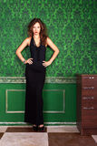 Gorgeous beautiful woman on a green vintage wall in evening dres Stock Photos