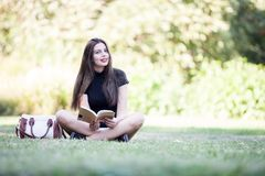 Gorgeous beautiful young woman reading a book in the pak Royalty Free Stock Photography