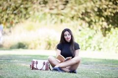 Gorgeous beautiful young woman reading a book in the pak Royalty Free Stock Images