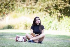Gorgeous beautiful young woman reading a book in the pak Royalty Free Stock Photo