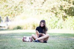 Gorgeous beautiful young woman reading a book in the pak Stock Images