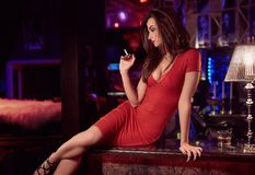 Gorgeous beauty young brunette woman in red dress with cigarette. Portrait of gorgeous beauty young brunette woman in red dress sitting at the bar with cigarette Royalty Free Stock Image