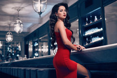 Gorgeous beauty young brunette woman in red dress. Standing at the bar in luxury interior Stock Photo