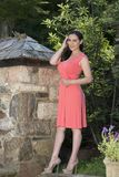 Gorgeous biracial woman poses wearing pink dress in garden Stock Images