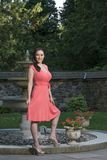 Gorgeous biracial woman poses wearing pink dress in garden Stock Image