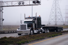 Gorgeous black big rig semi truck flat bed trailer devided road Stock Images
