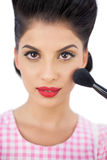 Gorgeous black hair model applying powder on her cheek Royalty Free Stock Image
