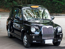 Gorgeous Black London Taxi cab. A Gorgeous Black London Taxi parked with the reflections of the greenery around caste on its shining new metal body Stock Photos