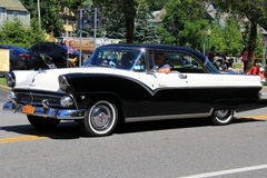 Gorgeous black and white car in Independence day parade,downtown Saratoga Springs, New York,2016. Crowds surrounding gorgeous black and white car rolling slowly Stock Photography