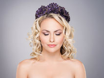 Gorgeous blond with closed eyes wearing a purple flower crown Stock Photography