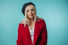 Gorgeous blond Frenchwoman in red coat. Closeup portrait of gorgeous blond Frenchwoman in red coat isolated on the blue background. clothers concept Stock Image