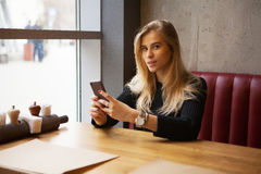 Gorgeous blond girl resting in cafe with iphone Stock Photos