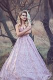 Gorgeous blond lady with luxuriant hairstyle in brocade ball gown standing at the dry leafless tree. Portrait of gorgeous blond lady with luxuriant hairstyle and Royalty Free Stock Images