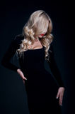 Gorgeous blond woman. Fashion portrait of pretty slim blond woman model with amazing figure wearing black tight cocktail dress, red lipstick, her hair made in Stock Photo