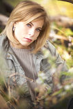 A gorgeous blond woman with greyish jacket sitting in grasses int he fall. Royalty Free Stock Image