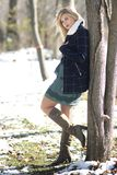 Gorgeous blond woman leaning against a tree with winter coat and high boots. Gorgeous blond woman leaning against a tree with a short teal dress and high boots royalty free stock photography