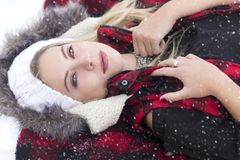 A gorgeous blond woman with piercing blue eyes laying in the snow with red plaid vest. A gorgeous blond woman with piercing blue eyes wearing a white knit hat Stock Photo