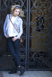 Gorgeous blond woman with sunglasses on head standing against rod iron gate. Stock Image