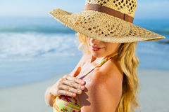 Gorgeous blonde in bikini applying suncream on the beach Stock Photography