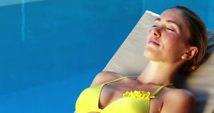 Gorgeous blonde in bikini enjoying the sunshine poolside stock footage