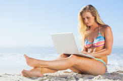 Gorgeous blonde in bikini using laptop on the beach Stock Photo