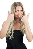 Gorgeous blonde in black dress thumbs up Royalty Free Stock Images