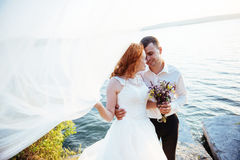 Gorgeous blonde bride and groom classy on the rocks, amid the se Royalty Free Stock Photos