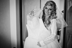 Gorgeous blonde bride posing with elegant wedding dress in hotel Stock Images