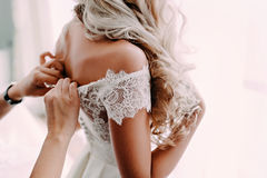 Gorgeous, blonde bride in white luxury dress is getting ready for wedding. Morning preparations. Woman putting on dress. Stock Photos