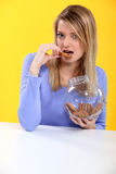 Gorgeous blonde eating cookies. Against yellow background Stock Image