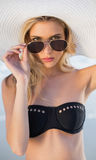 Gorgeous blonde in elegant black bikini looking over her sunglasses Royalty Free Stock Images