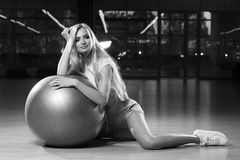 Blonde woman in sports clothing posing with silver yoga ball. Gorgeous blonde female model, dressed in crop top, blue shorts and white trainers, sitting on Royalty Free Stock Photography