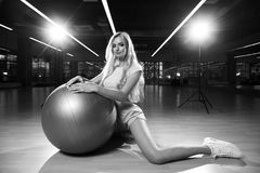 Blonde woman in sports clothing posing with silver yoga ball. Gorgeous blonde female model, dressed in crop top, blue shorts and white trainers, sitting on Royalty Free Stock Image