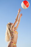 Gorgeous blonde in floral bikini throwing beach ball Stock Photos