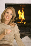 Gorgeous blonde in front of fireplace vertical Royalty Free Stock Images