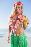 Gorgeous blonde in garland and grass skirt holding cocktail on the beach Stock Photos