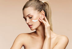 Gorgeous blonde girl applying moisturizing cream on her face. stock images