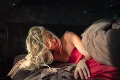 Gorgeous blonde girl wake up in the bed and relaxes at early morning. Young sleepy woman is smiling in stylish bedroom in sunny day royalty free stock image