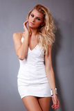 Gorgeous Blonde girl in white dress. Beautiful fashion female model in white dress is posing on gray background Stock Photo
