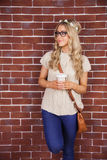 Gorgeous blonde hipster leaning against red brick background Royalty Free Stock Photography