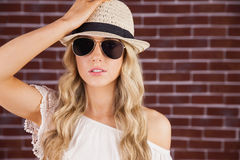 Gorgeous blonde hipster posing with straw hat Royalty Free Stock Image